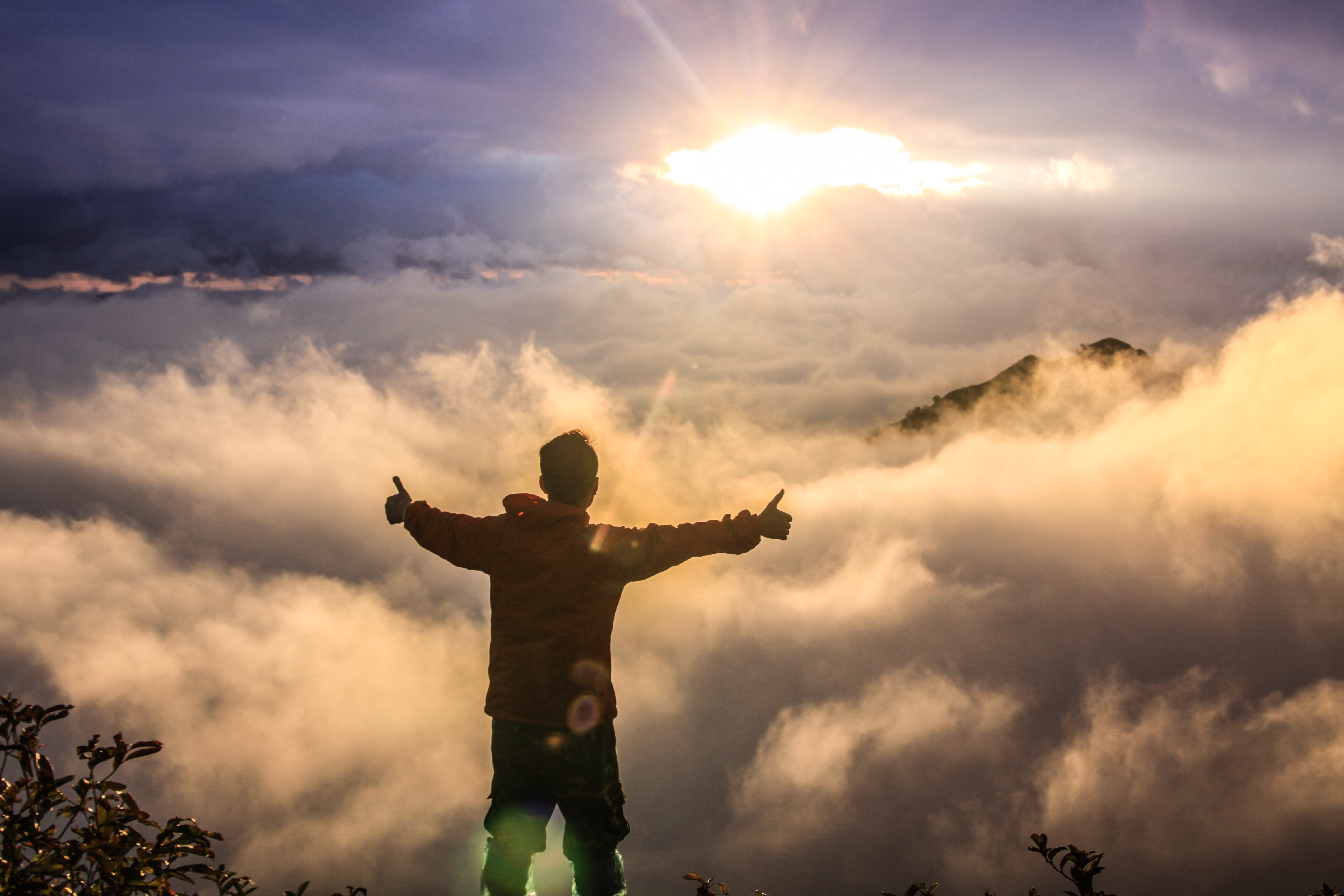 Never Settle. Man Standing In Victory Among The Clouds