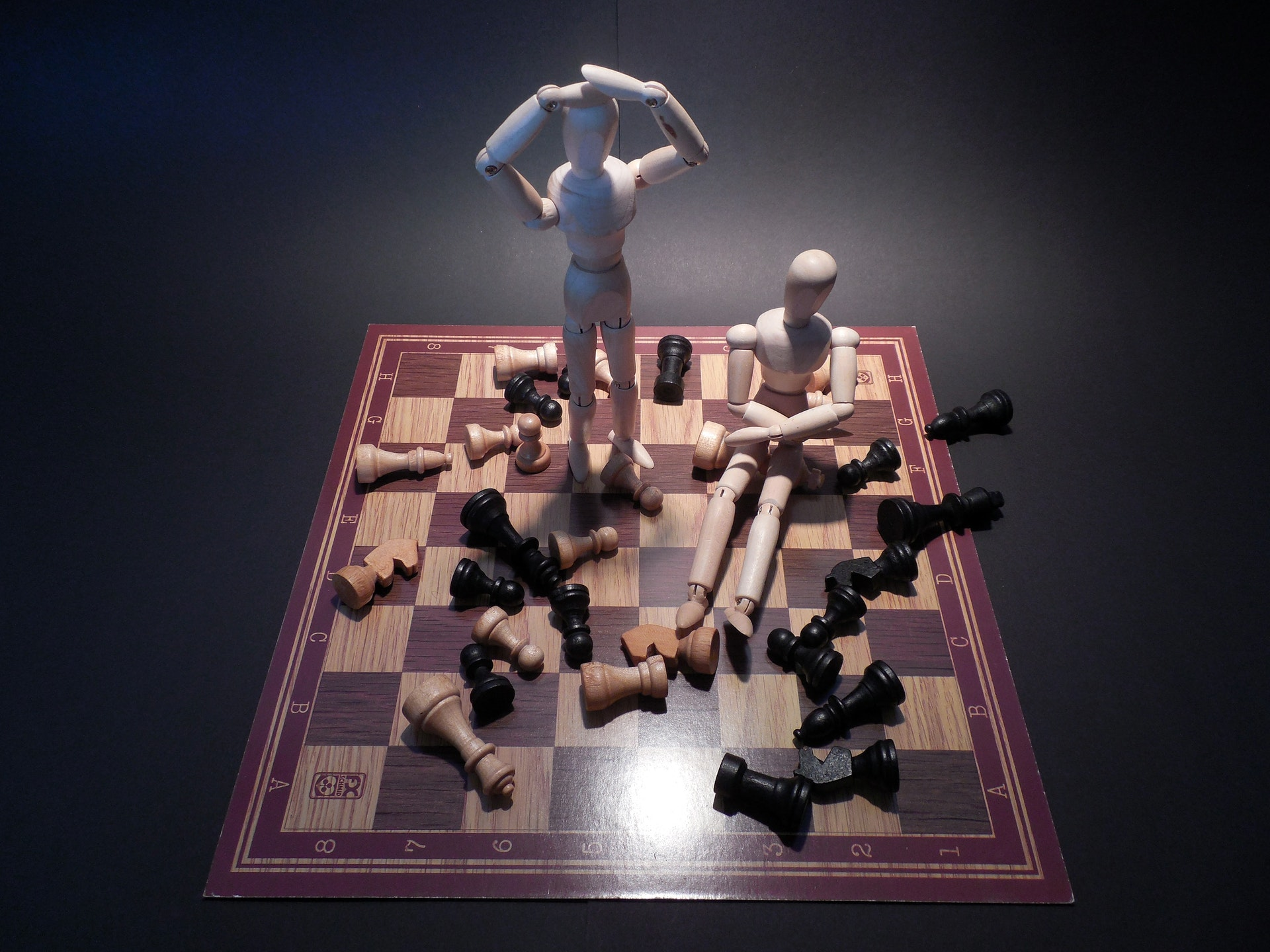 Two wooden dolls on a chess board symbolizing a problem