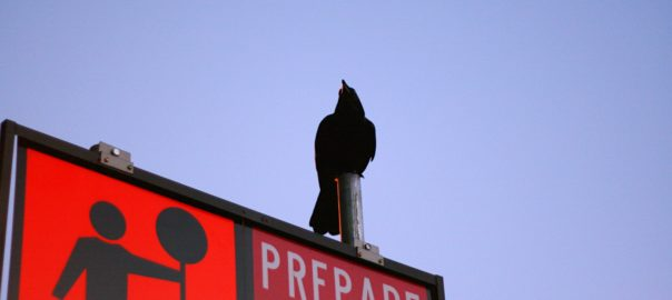Sign With Figure On Top That Says Prepare
